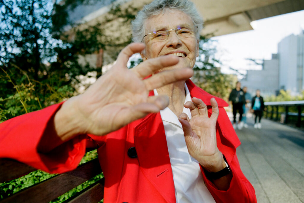 woman with grey hair and red jacket holding her hand up at the camera