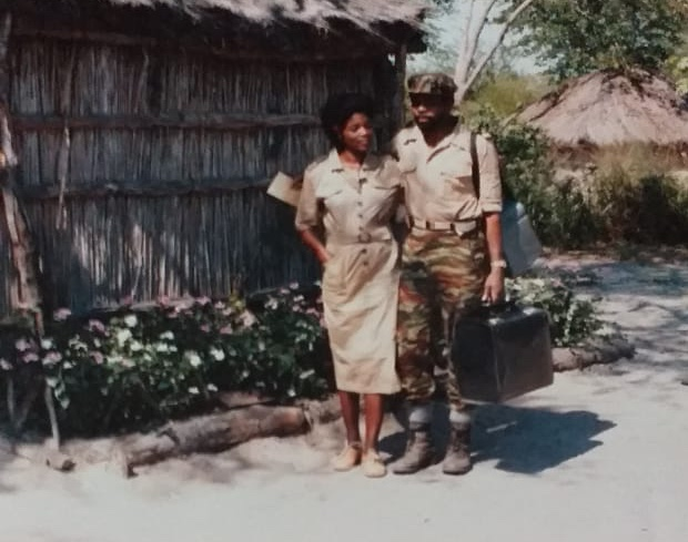 Man and woman in military uniforms in front of bamboo house