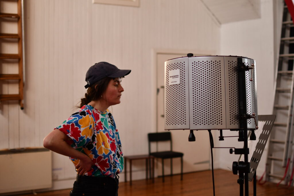 Woman with cap on standing in front of shielded microphone