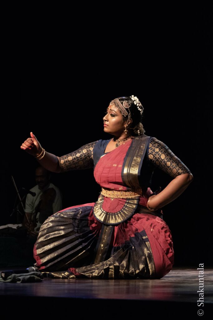 Woman dancer kneeling and gesturing with hand and finger
