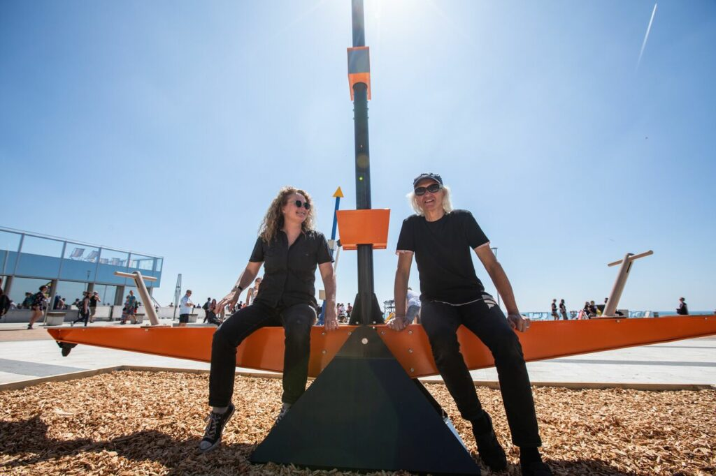 A man and a woman sit on a seesaw artwork outside in the sun. They both wear black.